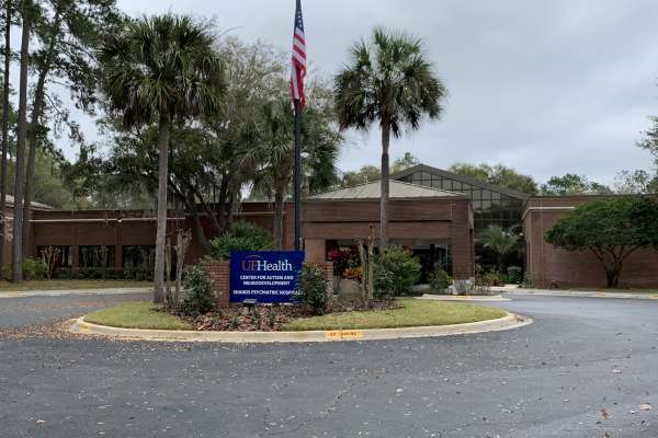 "One story brick building with a circular driveway. In front of the building is a flag pole with an American flag and a sign that says, ""UF Health, Center for Autism and Neurodevelopment, Shands Psychiatric Hospital"""