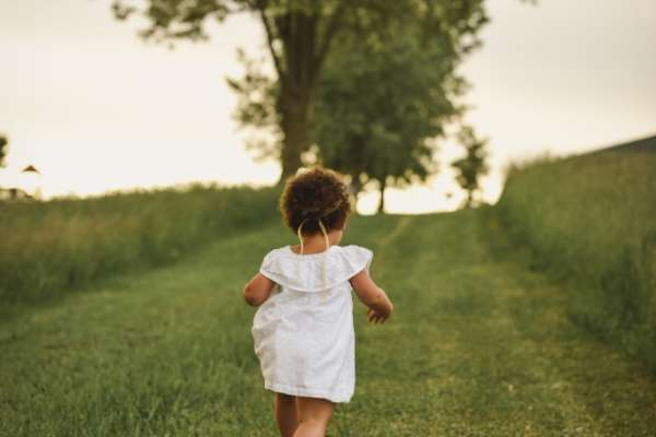 Young girl in a white and no shoes running up grassy hill toward a tree