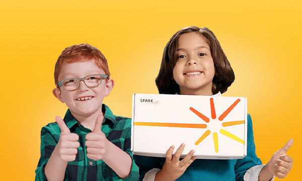 Young children; one is holding cardboard box that says SPARK on it