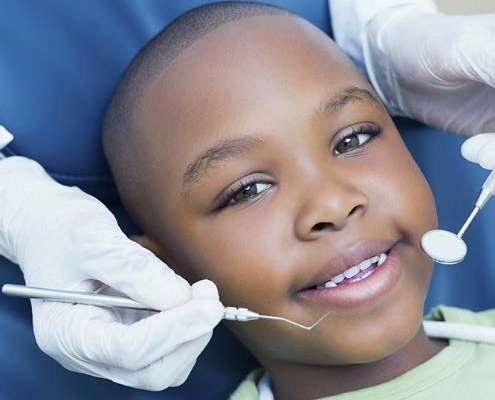young child in a with a dentist behind him holding dental tools near his mouth