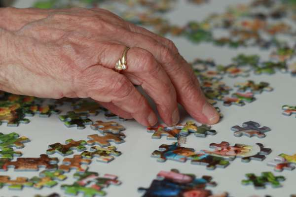 elderly person's hand and puzzle pieces