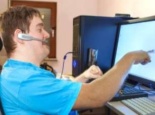 man siting in front of computer pointing at screen