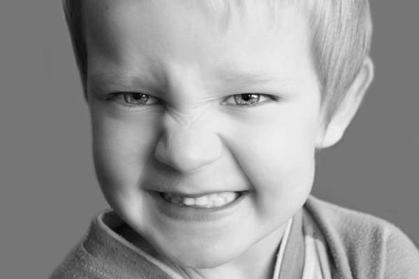 young boy showing teeth and snarling